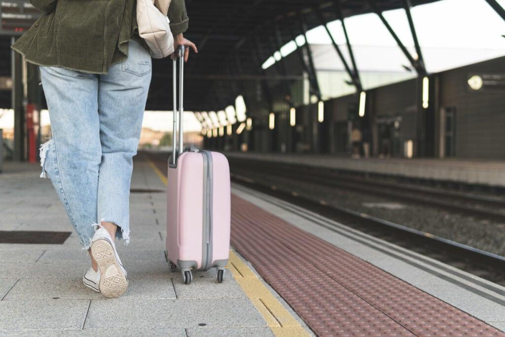 Frau mit Koffer am Bahnsteih