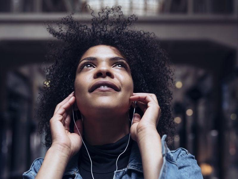 Schwarze frau hört musik über kopfhörer