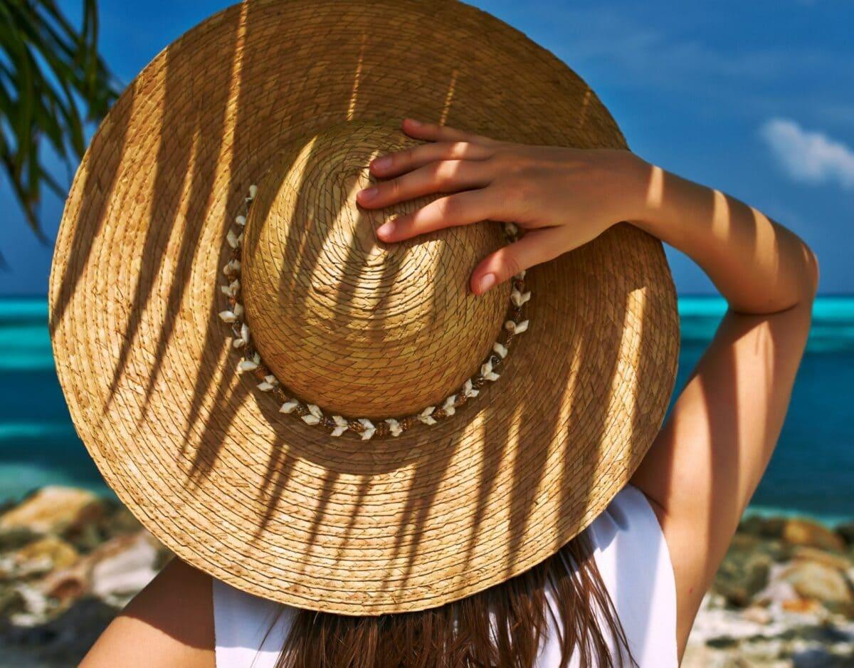 frau am strand mit sonnenhut