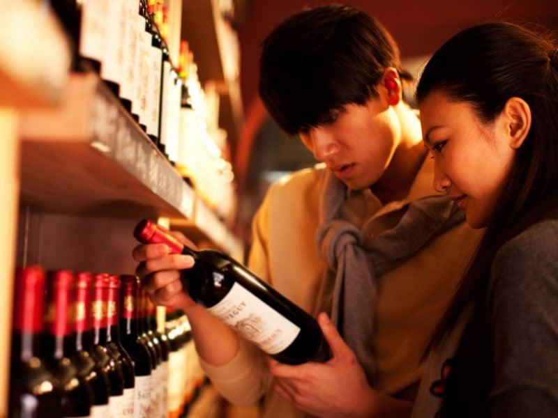 rotwein kaufen asiaten frau mann weinflasche trinken