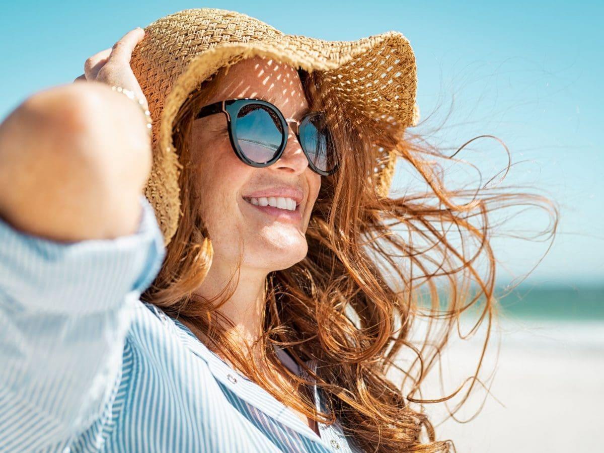 Frau am Strand mit Sonnenbrille und Hut, Haare wehen im Wind, vitamine für haare