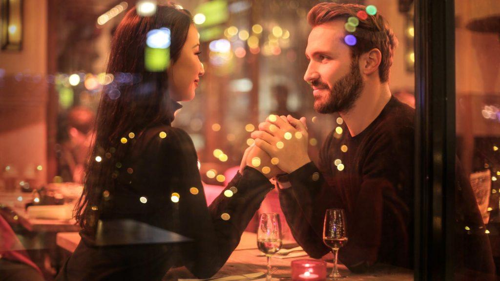 Ein Pärchen sitzt in einem Restaurant bei einem  Date hält Händchne
