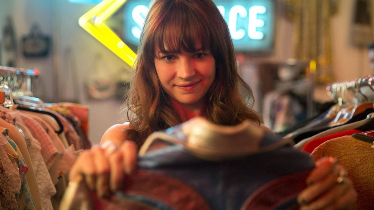 Girlsboss Schauspielerin hält ein Kleidungsstück in der Hand