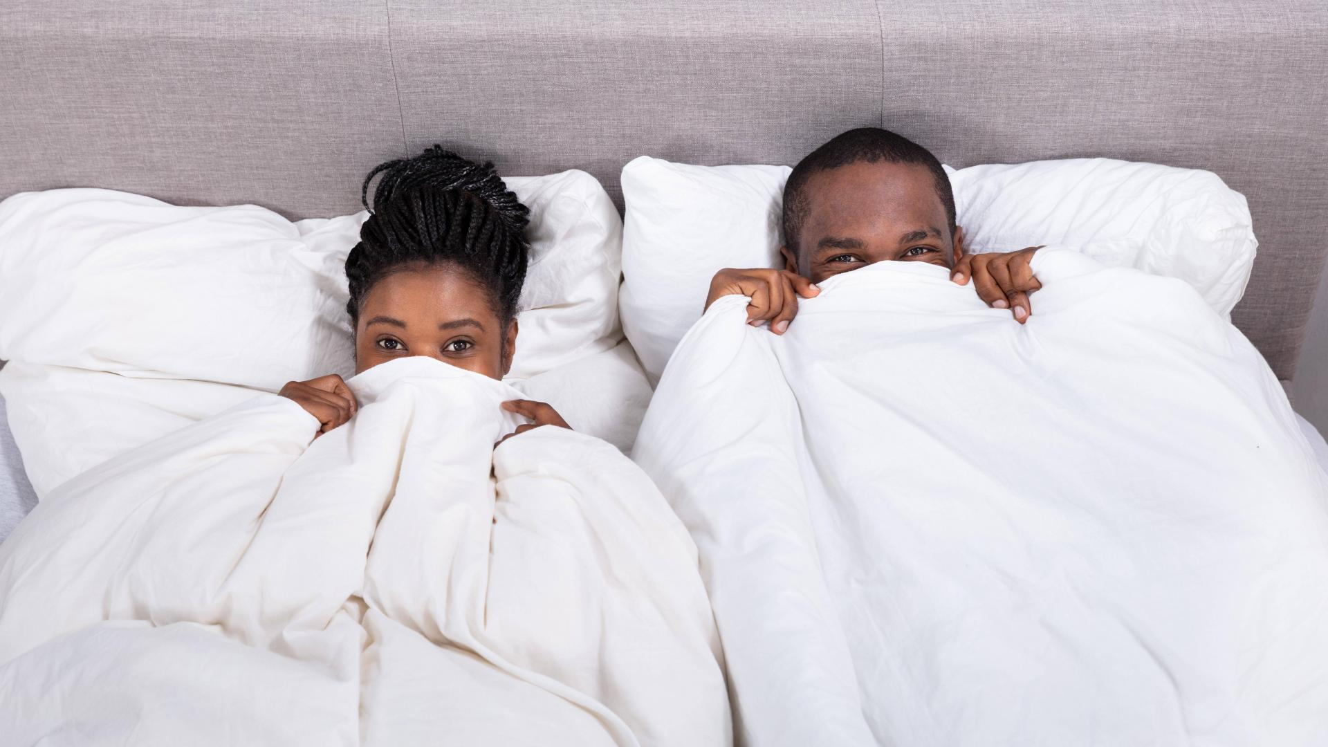 Pärchen im Bett, Decke über dem Kopf