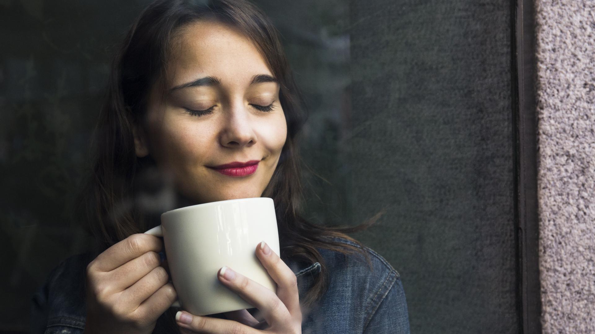 Frau lächelt mit geschlossenen Augen und ihrer Tasse Alternativen Kaffee in der Hand