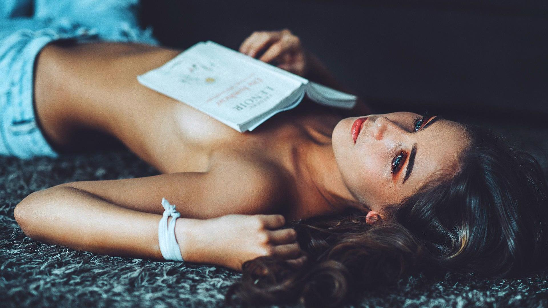 FRau liegt auf dme Bett mit Buch