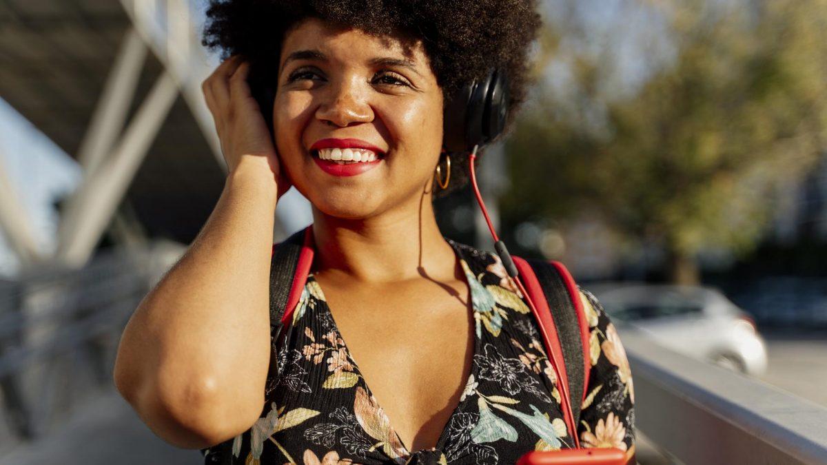 Frau hört Musik und lacht