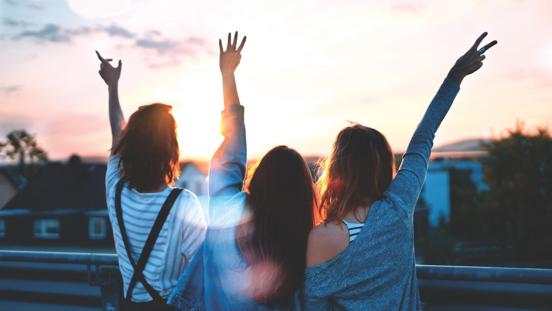 Drei junge Frauen recken die Hände in die Abendsonne
