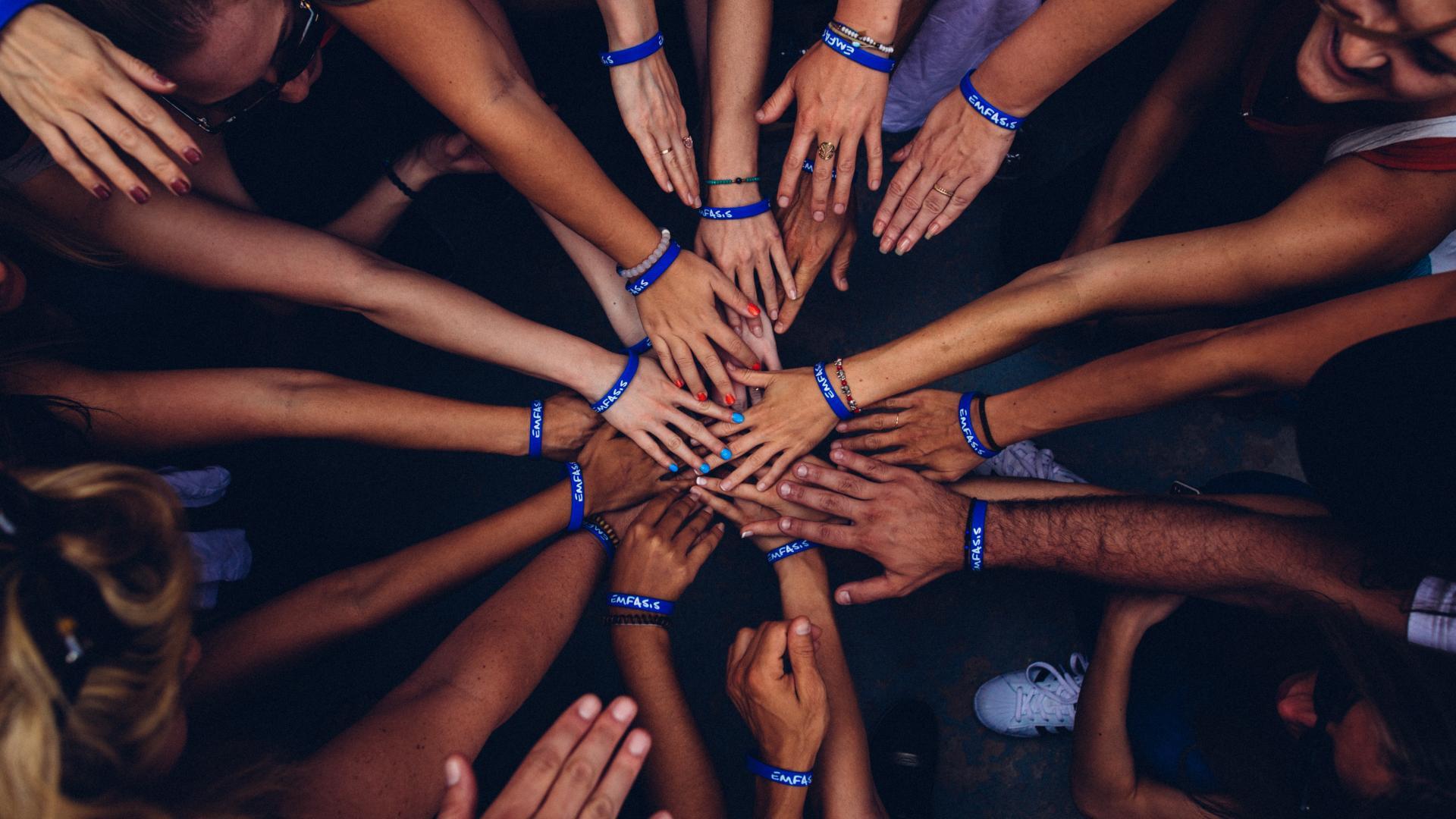 Gruppe von Menschen stecken die Hände zusammen