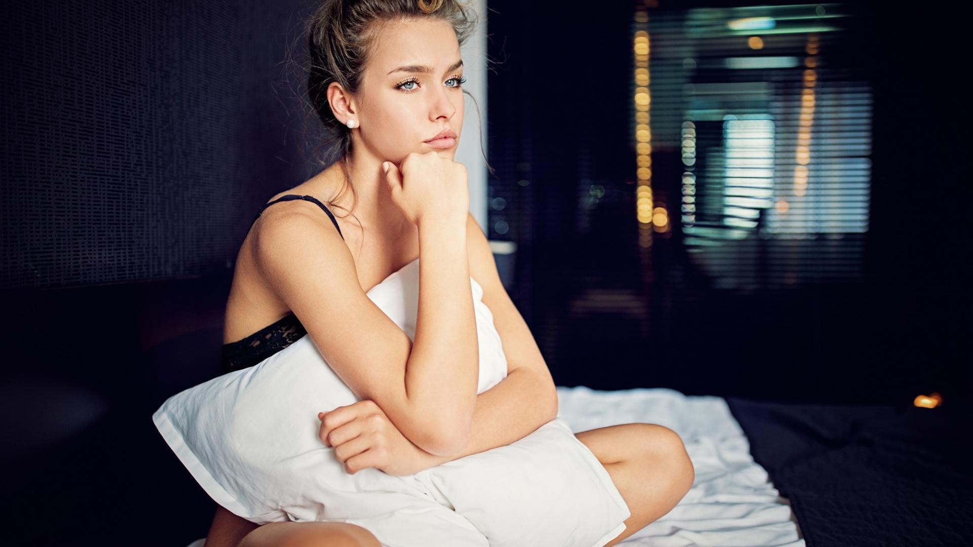 Frau sitzt in Unterwäsche auf dem Bett