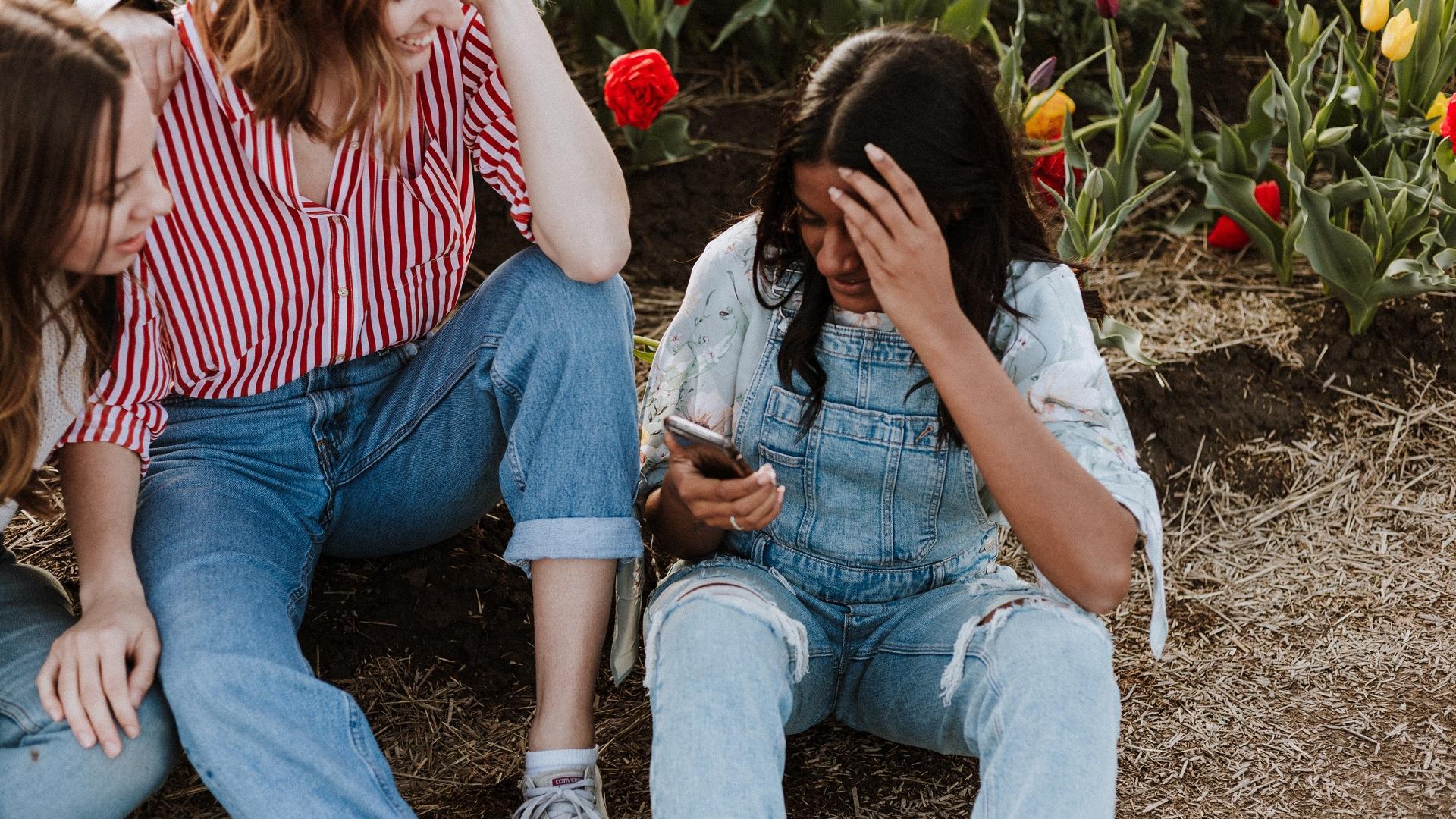 Tinder Tipps richtig anschreiben: Mädchen sitzen zusammen und lachen
