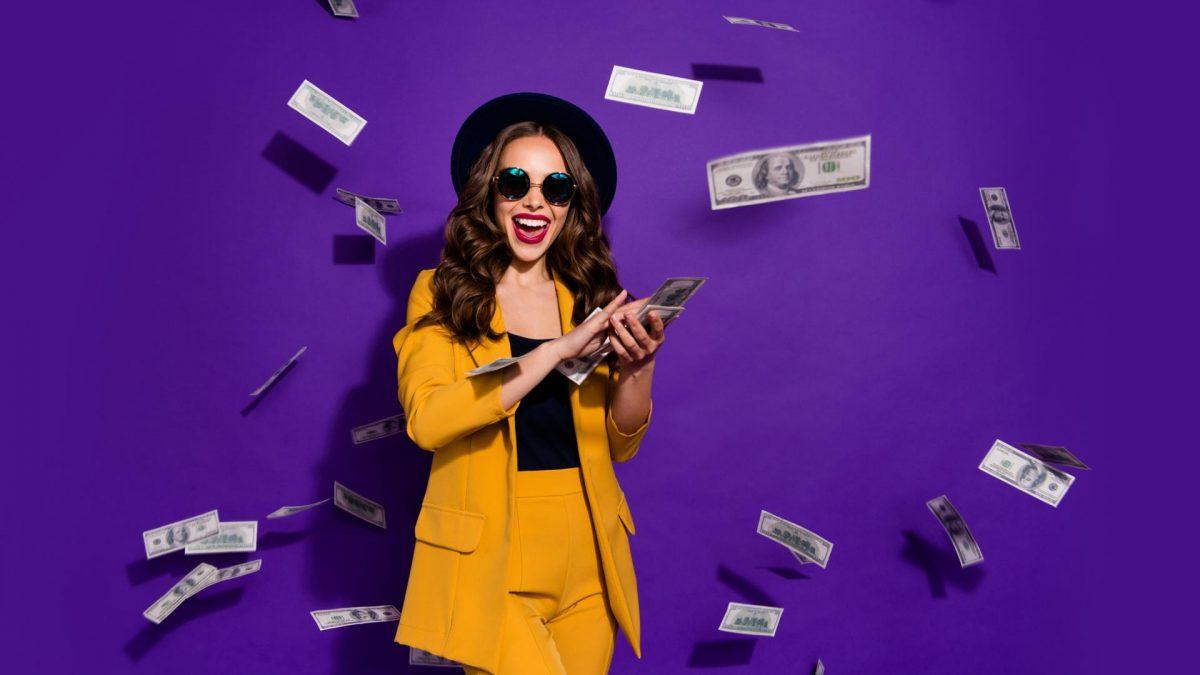 glückliche Frau im senfgelben Anzug vor lila Hintergrund wirft Dollarscheine durch die Luft