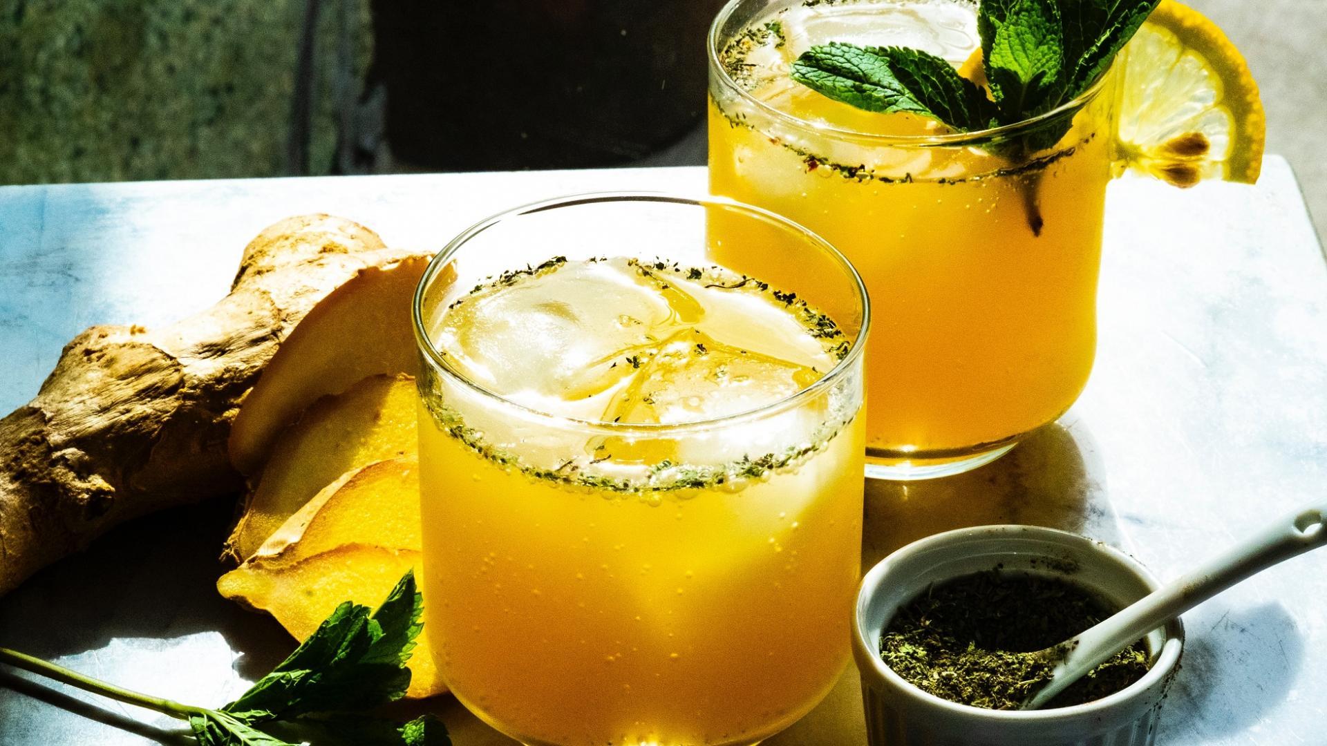 zwei Gäser mit Ingwergetränk und Zitrone auf einem Tisch
