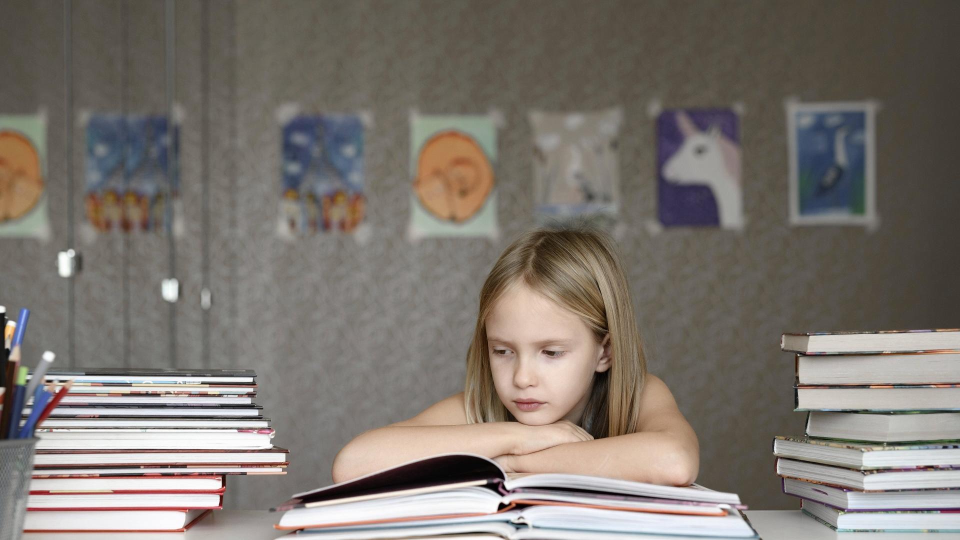 Mädchen sitzt genervt über Schulbüchern