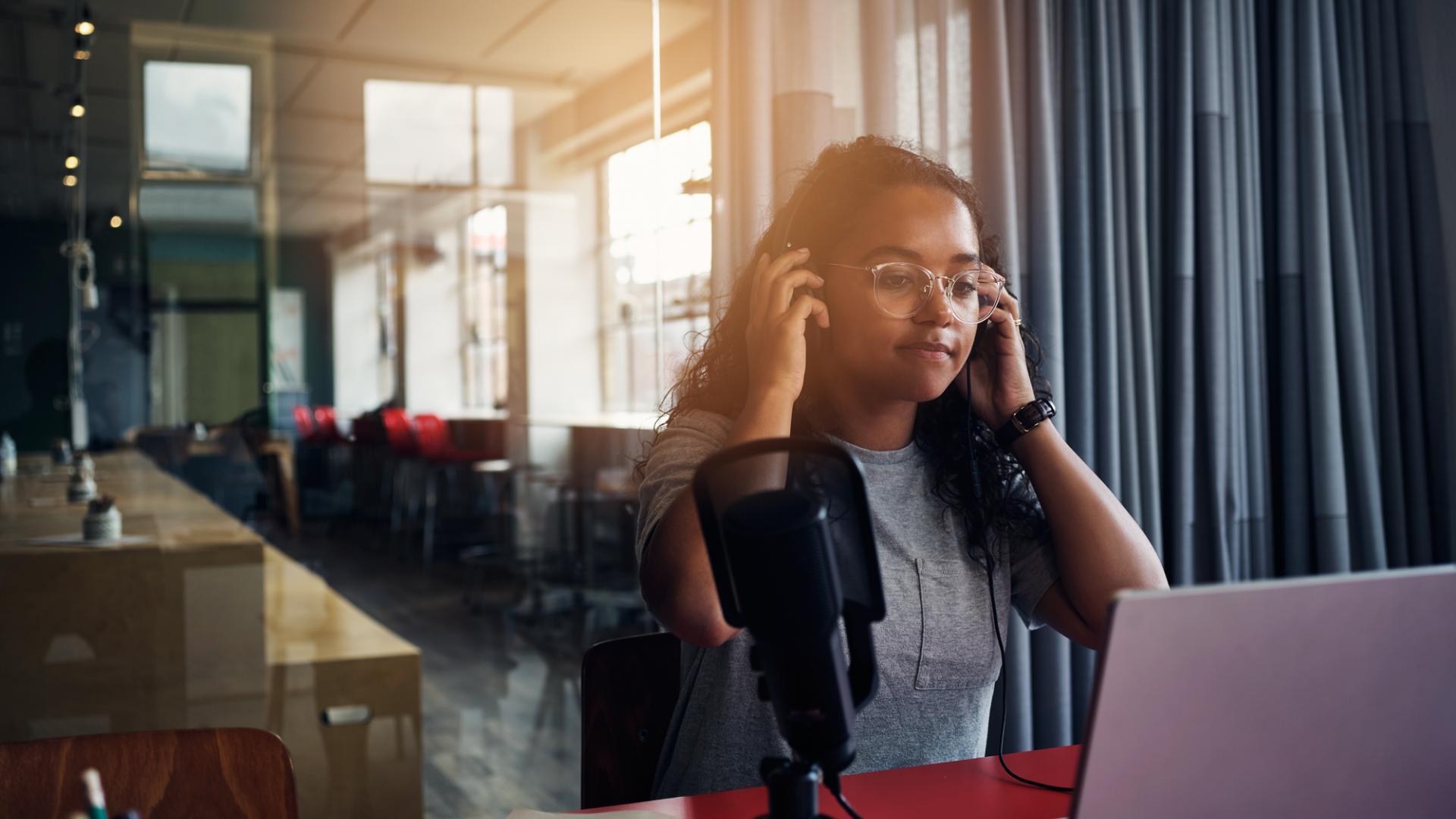 Frau mit Kopfhörern, Laptop, Arbeiten