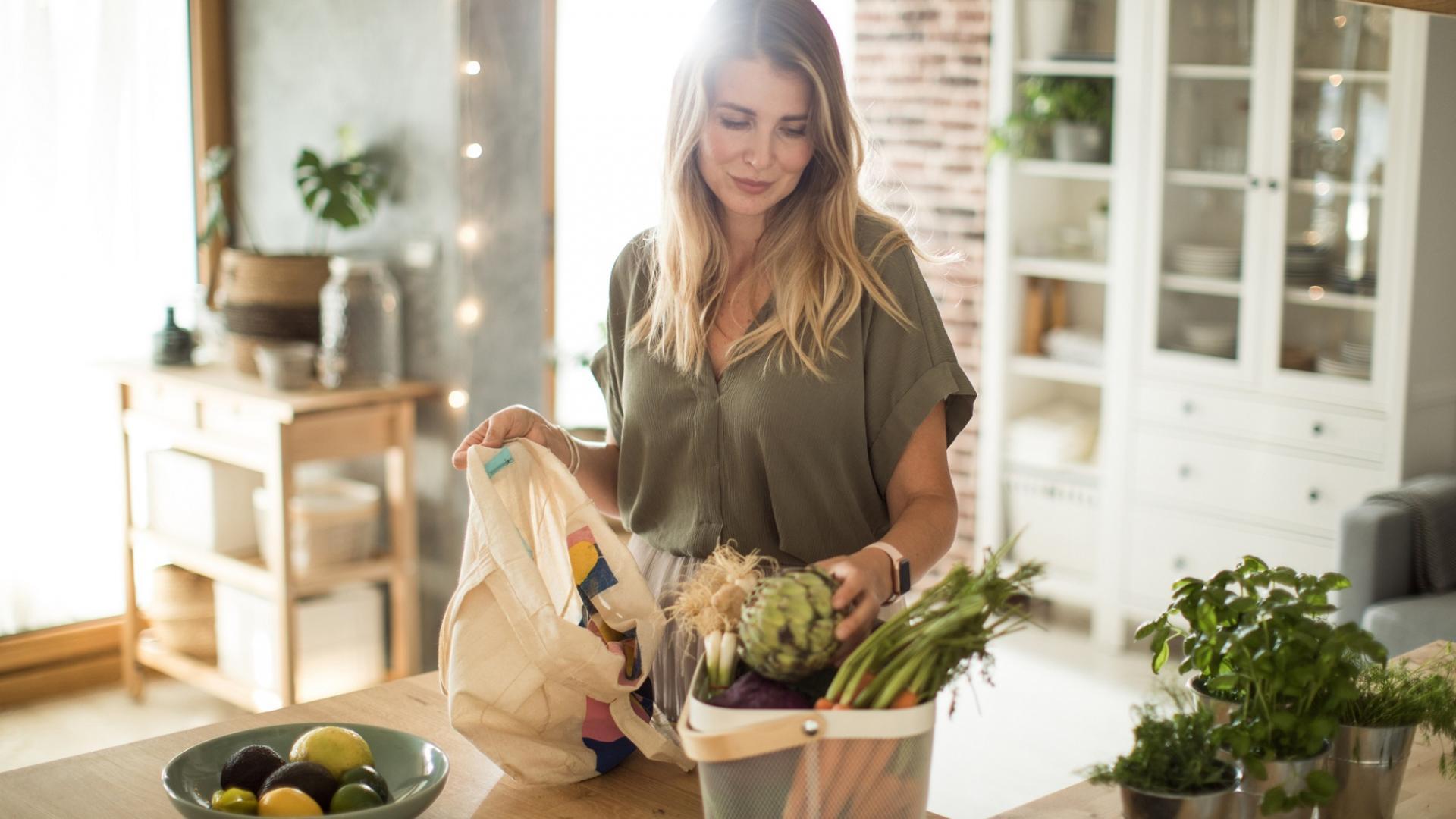 Lächelnde Frau in olivgrünen Shirt in Küche mit Gemüse