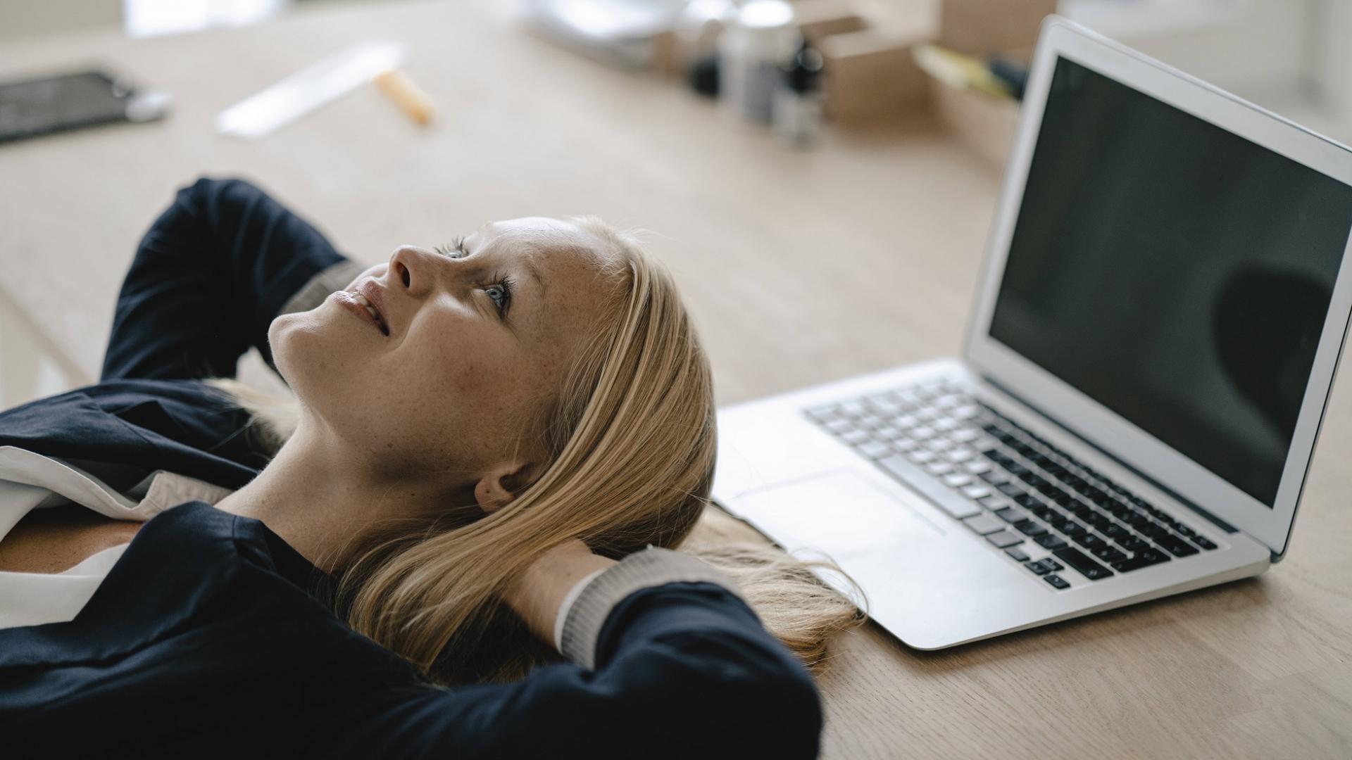 junge Business-Frau lächelt und macht eine Pause am Schreibtisch und legt ihren Kopf auf den Tisch vor dem Laptop