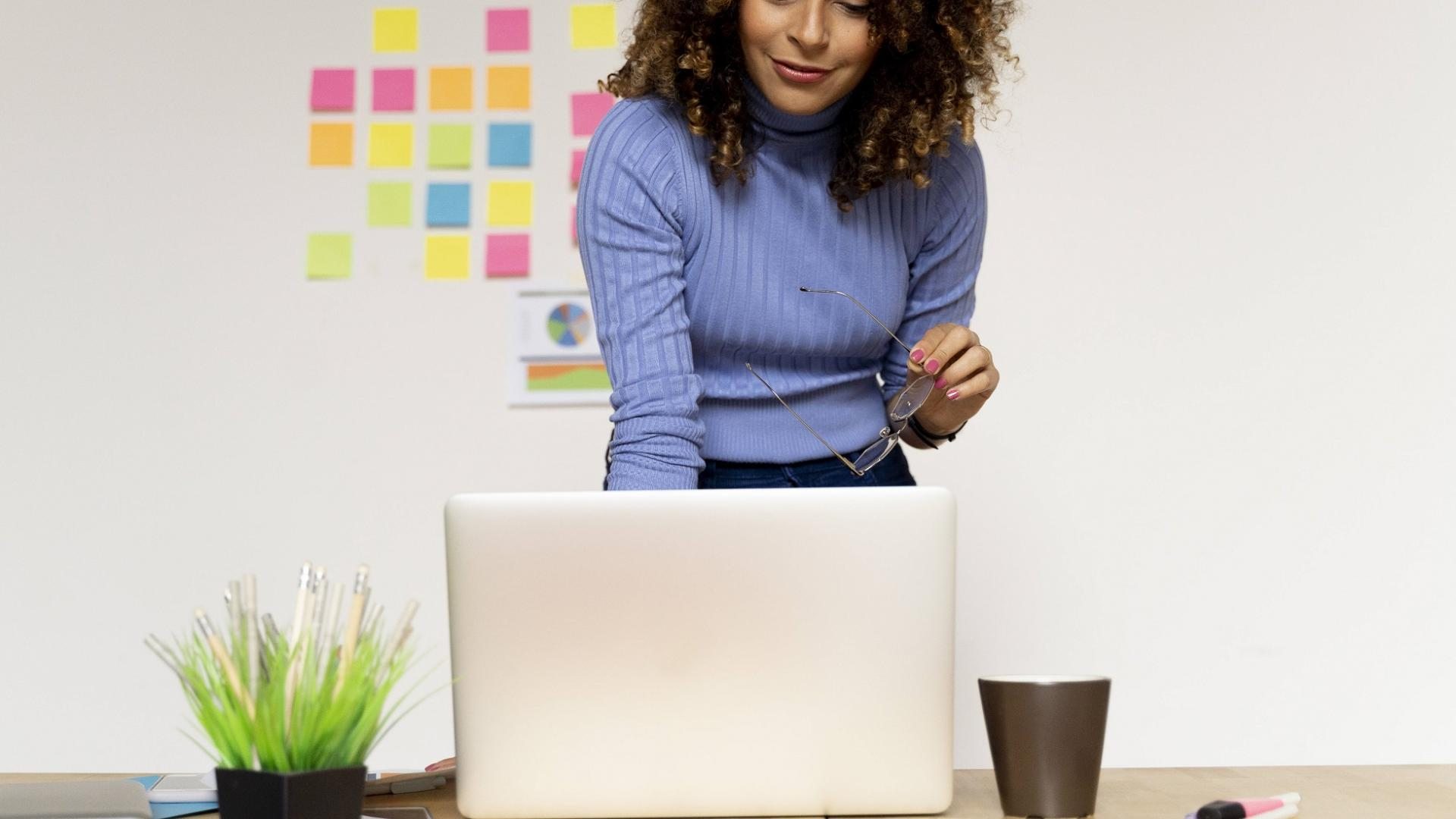 lächelnde junge Frau steht vor ihrem Laptop am Schreibtisch