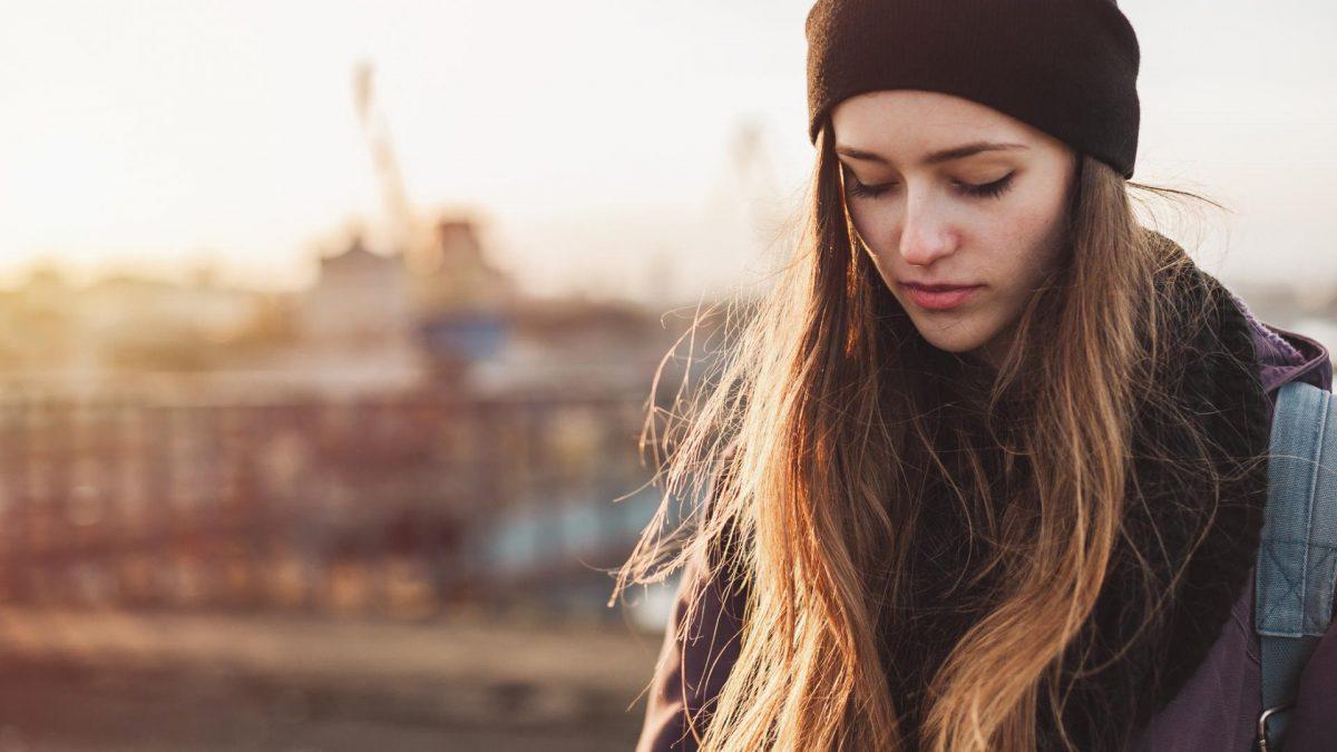 Frau mit Mütze fraußen, traurig, konzentriert