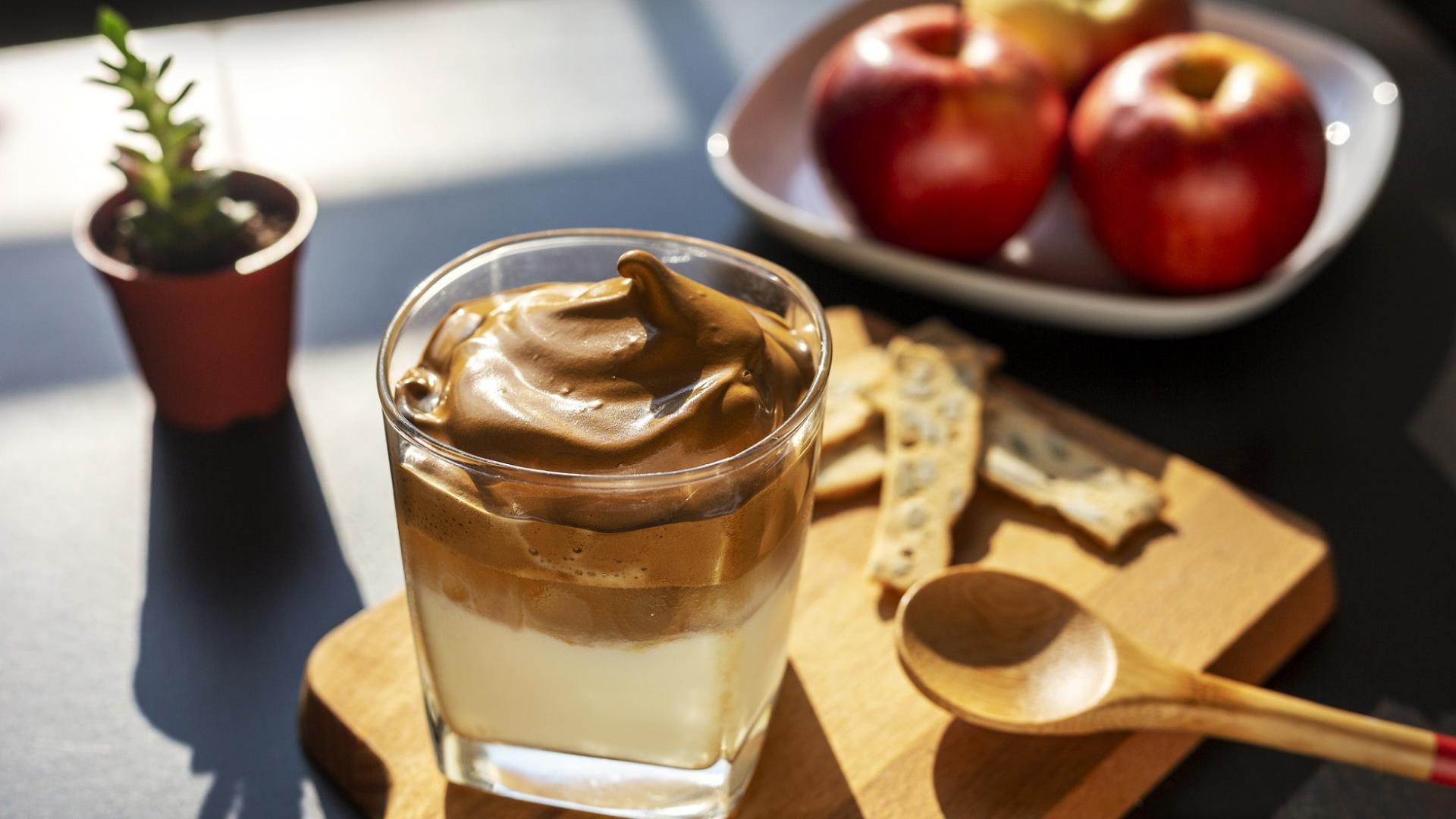 Dalgona Kaffe aus fluffiger Creme und Kaffee auf einem Holzbrett mit Löffel neben einer Schale mit Äpfeln