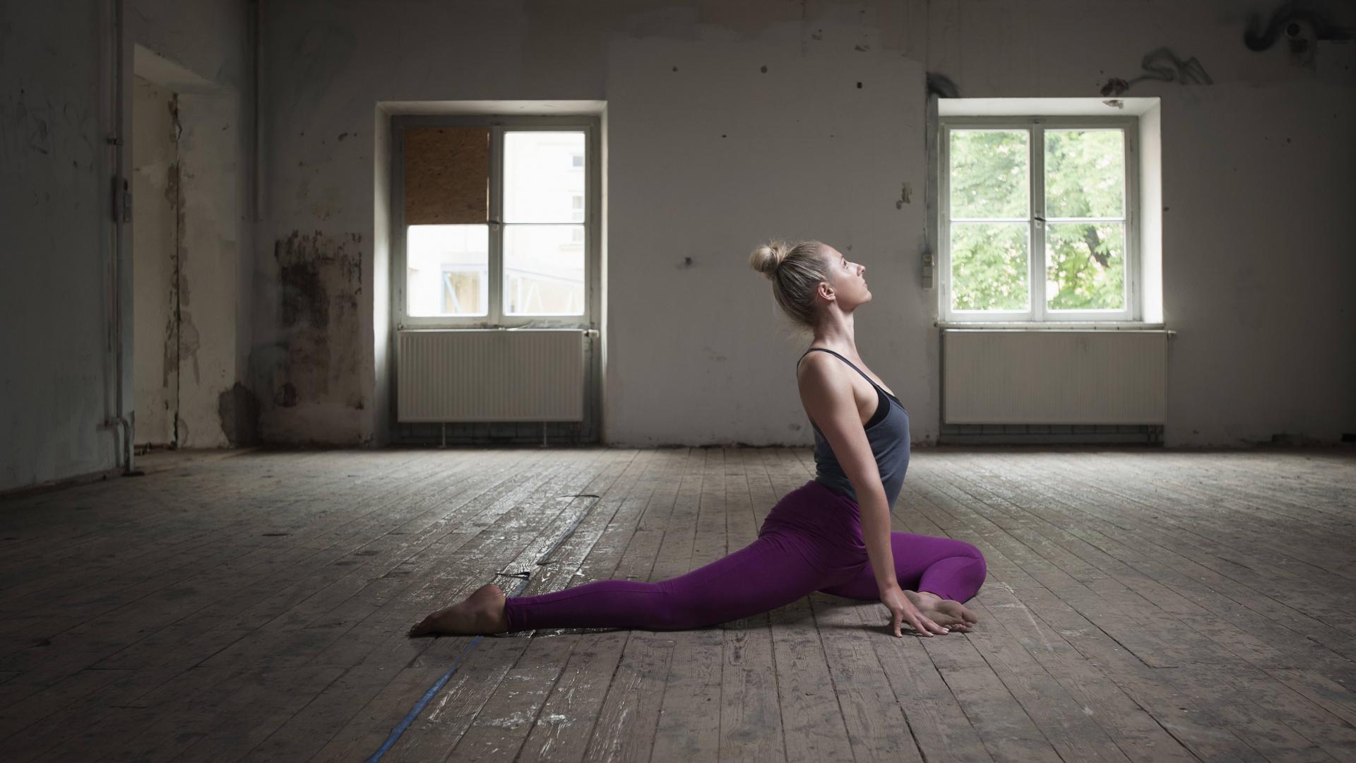 Frau in Yoga-Taubenstellung in einer alten verlassenen Wohnung