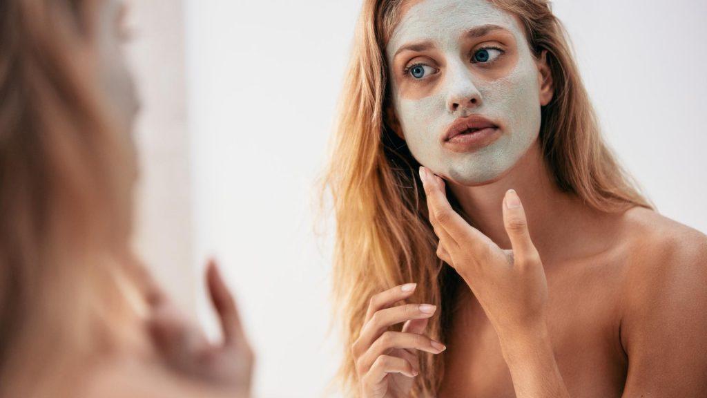 Frau vor dem Spiegel mit Gesichtsmaske