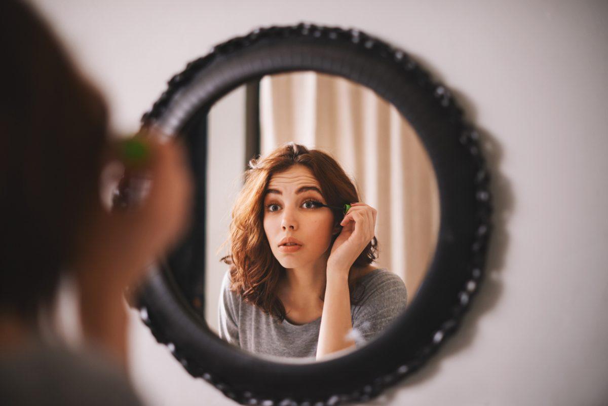 Frau trägt Make Up vor dem Spiegel auf
