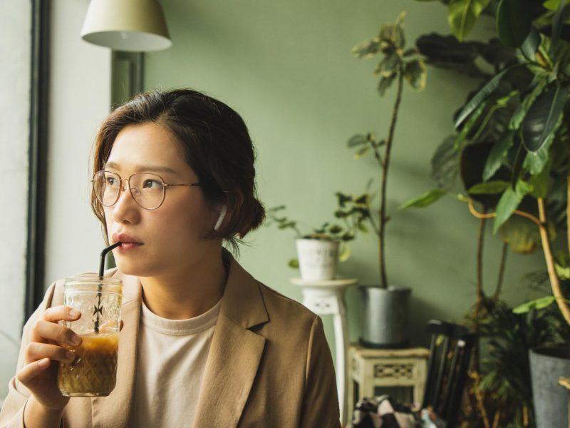 Asiatische junge Frau Podcast Getränk