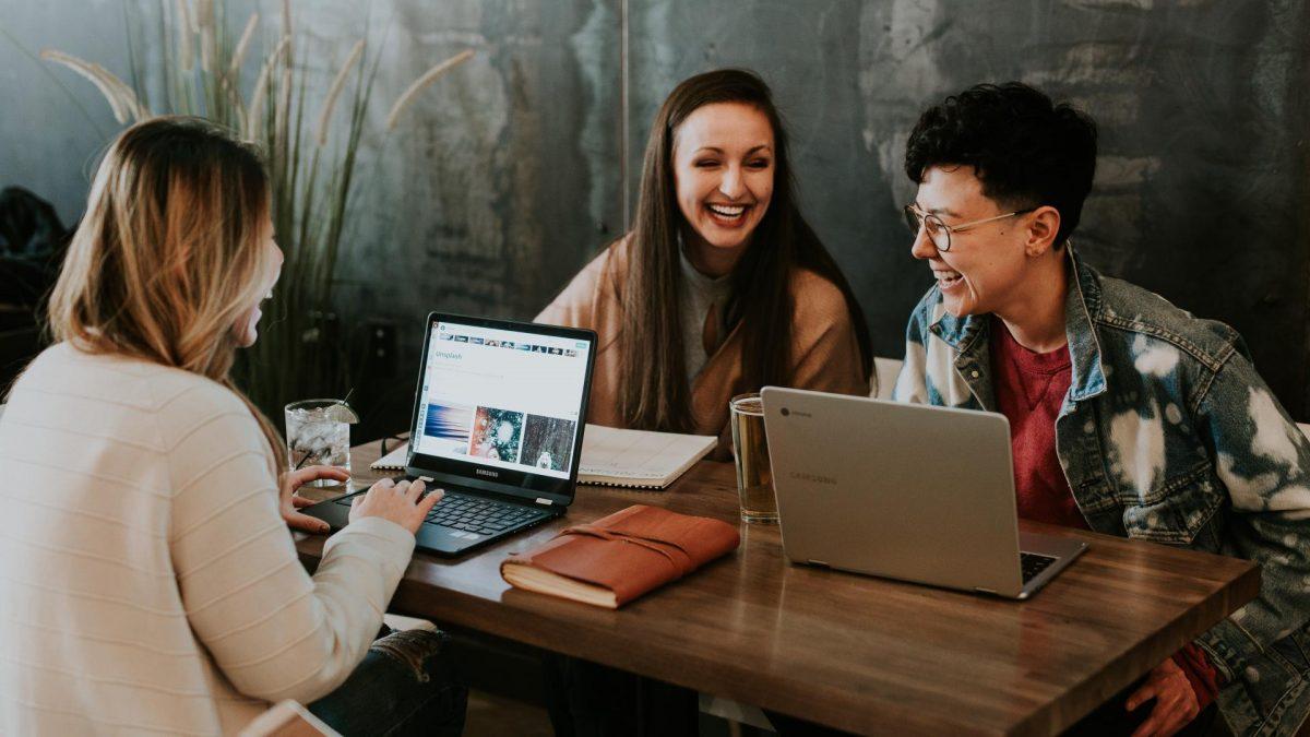 Drei Frauen sitzen lachend um einem Tisch mit ihren Laptops