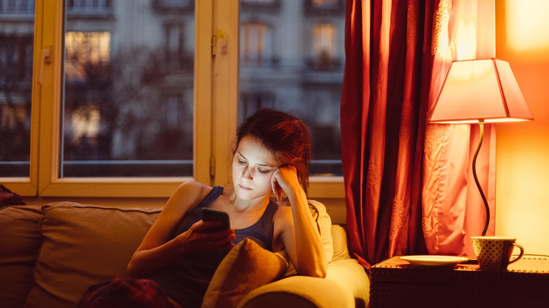 Frau am Handy traurig