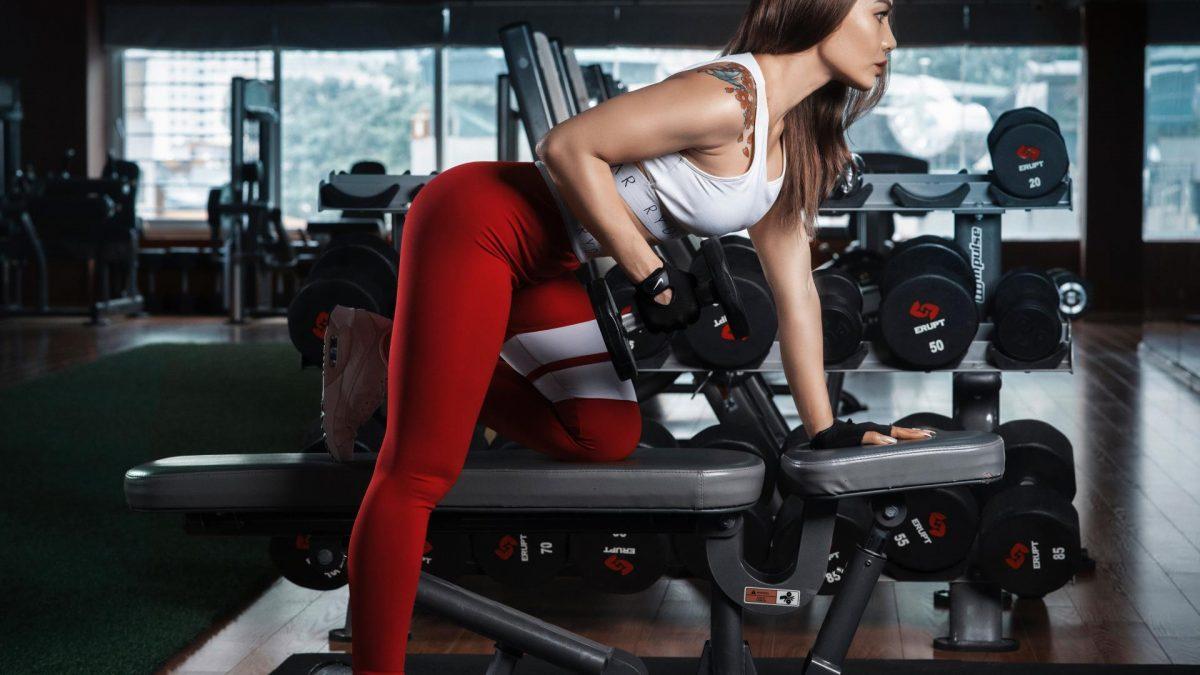 Frau im Fitnessstudio Vergleich beim Hantelnhebel