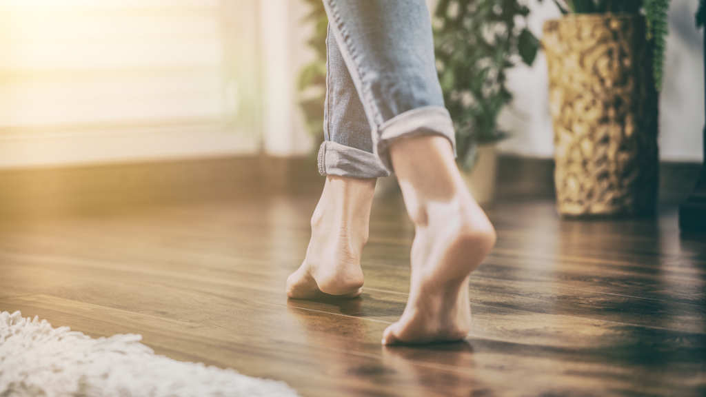 Frau läuft barfuß über Holzboden
