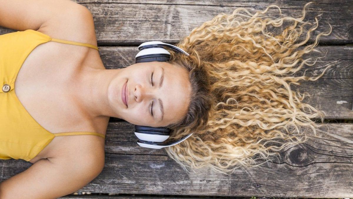 Frau liegt mit geschlossenen augen und lächelt während sie einen Psychologie-Podcast hört