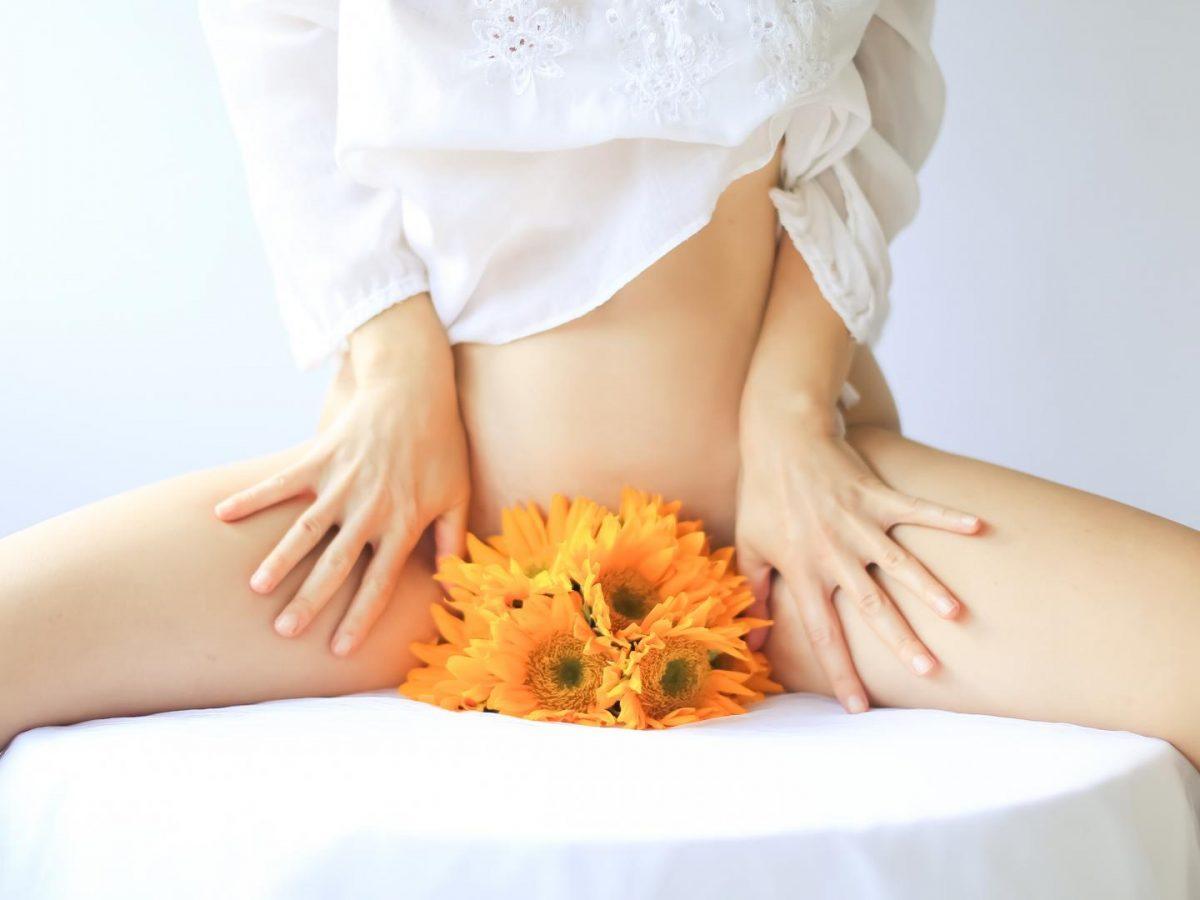 Frau mit Blumen zwischen den Beinen