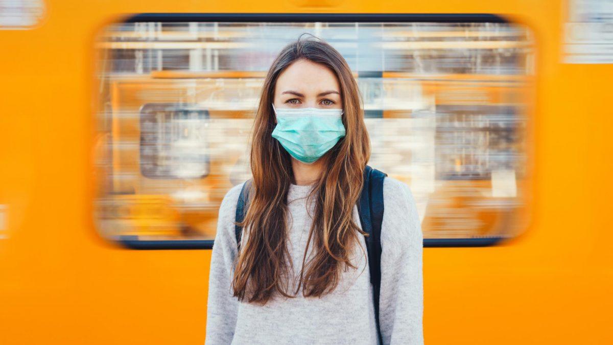 Frau mit Corona Maske vor Bahn