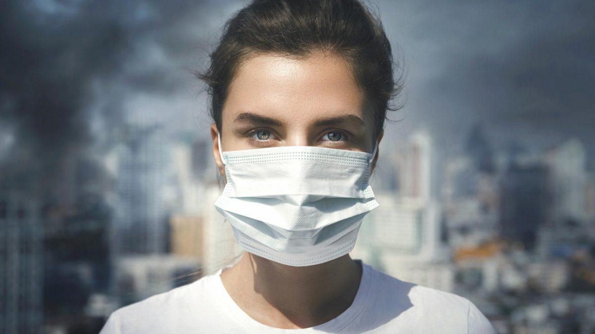 Frau mit Mundschutz vor Stadtkulisse
