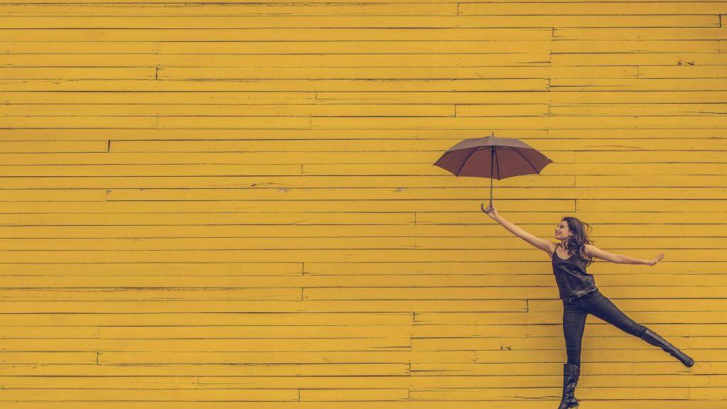 Frau mit Regenschirm vor gelben Holzdielen