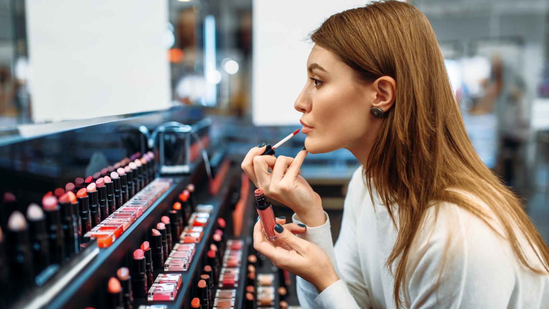 Frau schminkt ihre Lippen im Laden