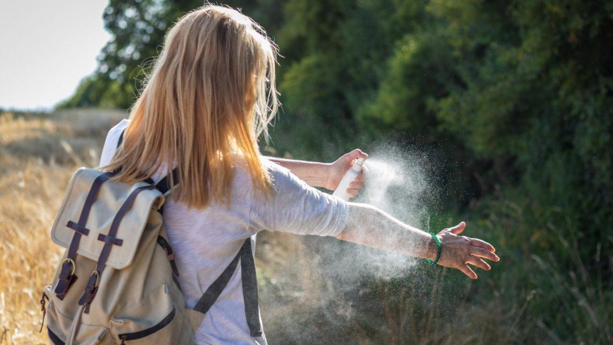 Frau sprüht sich mit Mückenspray ein