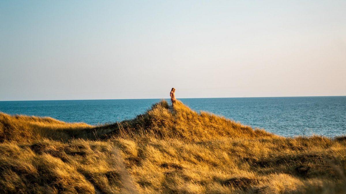 Frau steht auf einer Düne an der Küste