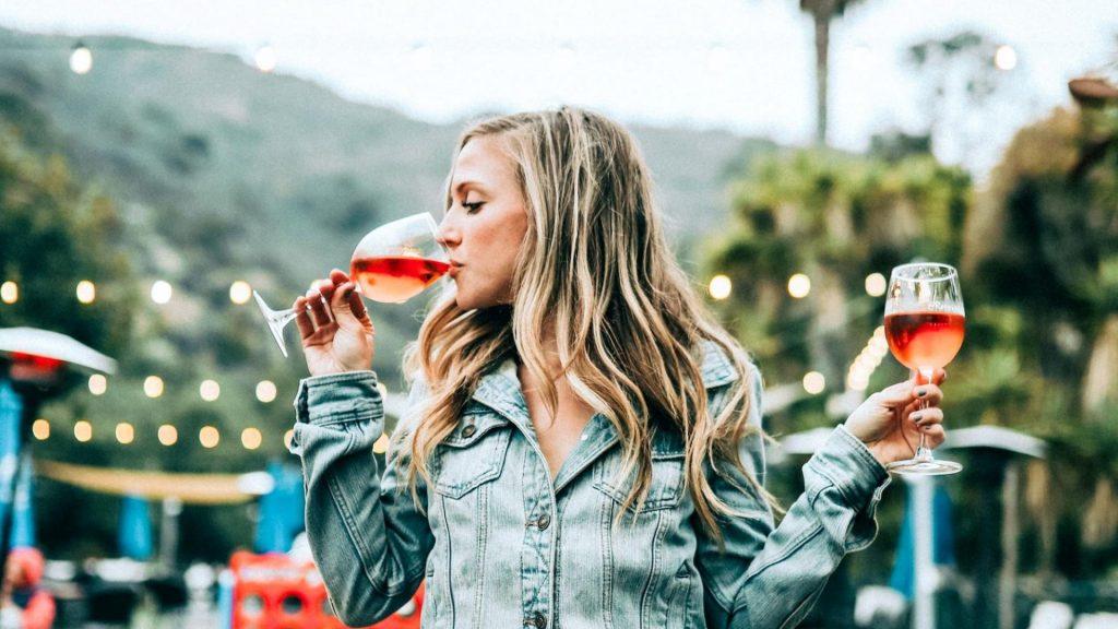 Frau trinkt zwei Gläser Wein