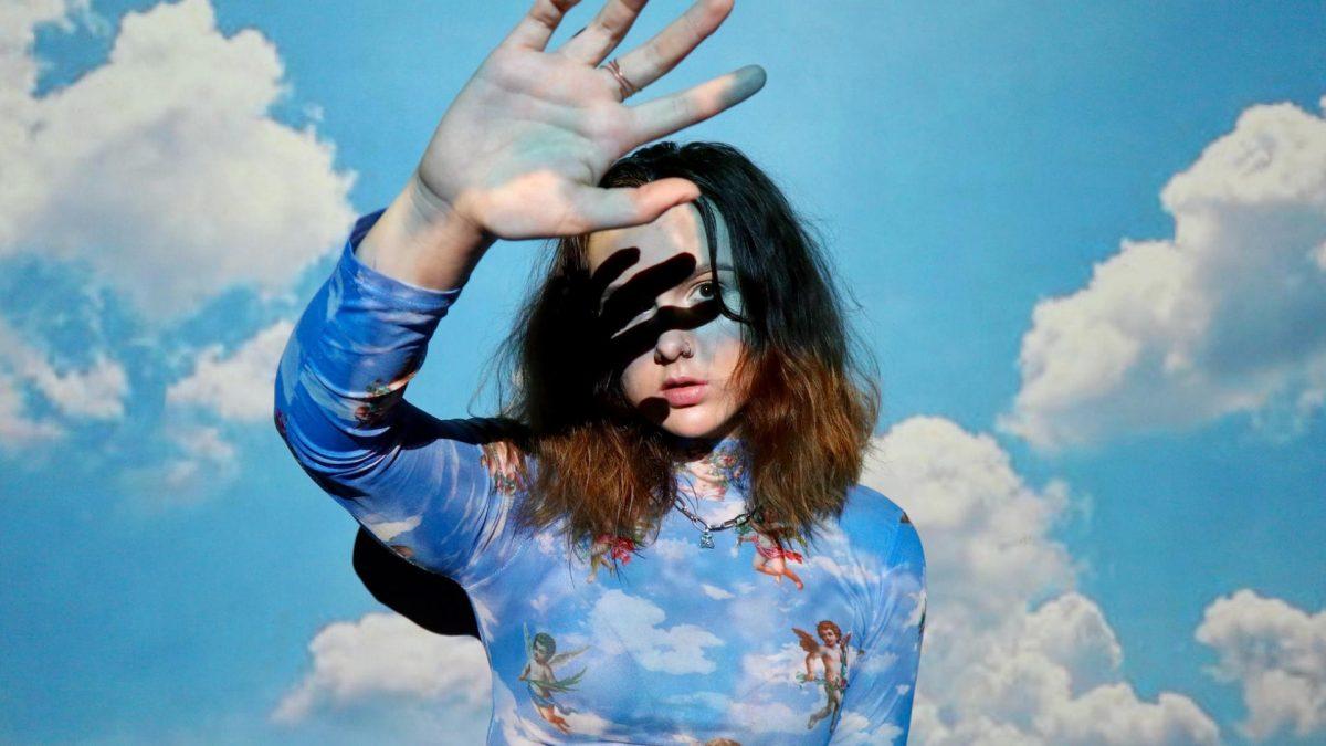 Frau vor blauem Wolkenhintergrund
