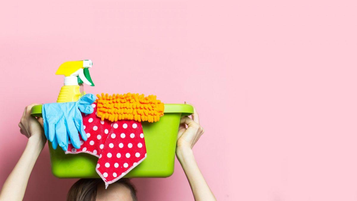 Frau vor rosa Hintergrund mit Box inklusive Putzmaterialien auf dem Kopf