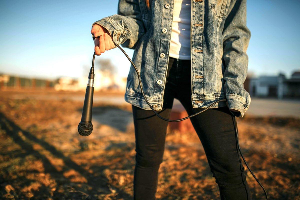 Junge Frau hält selbstbewusst ein Mikrofon