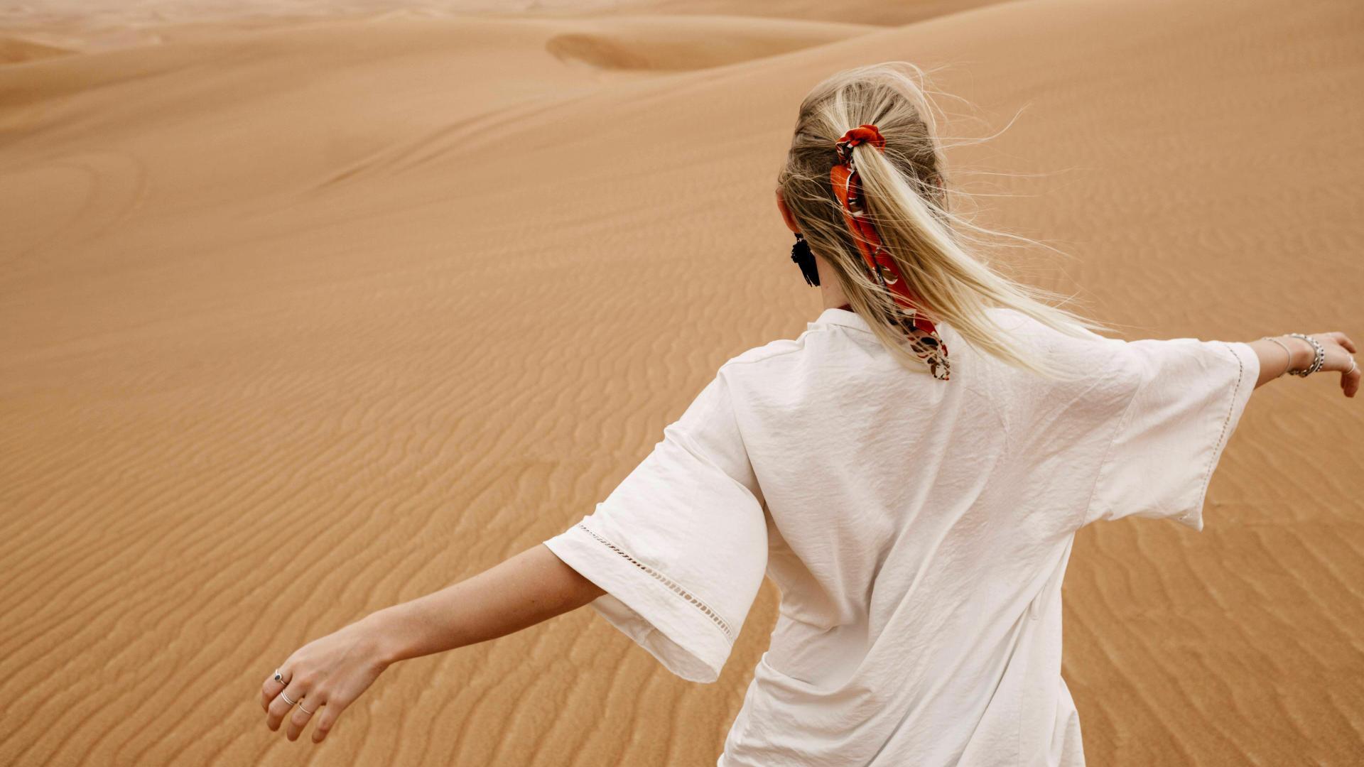 Junge Frau ist allein verreist und läuft fröhlich durch eine Wüste