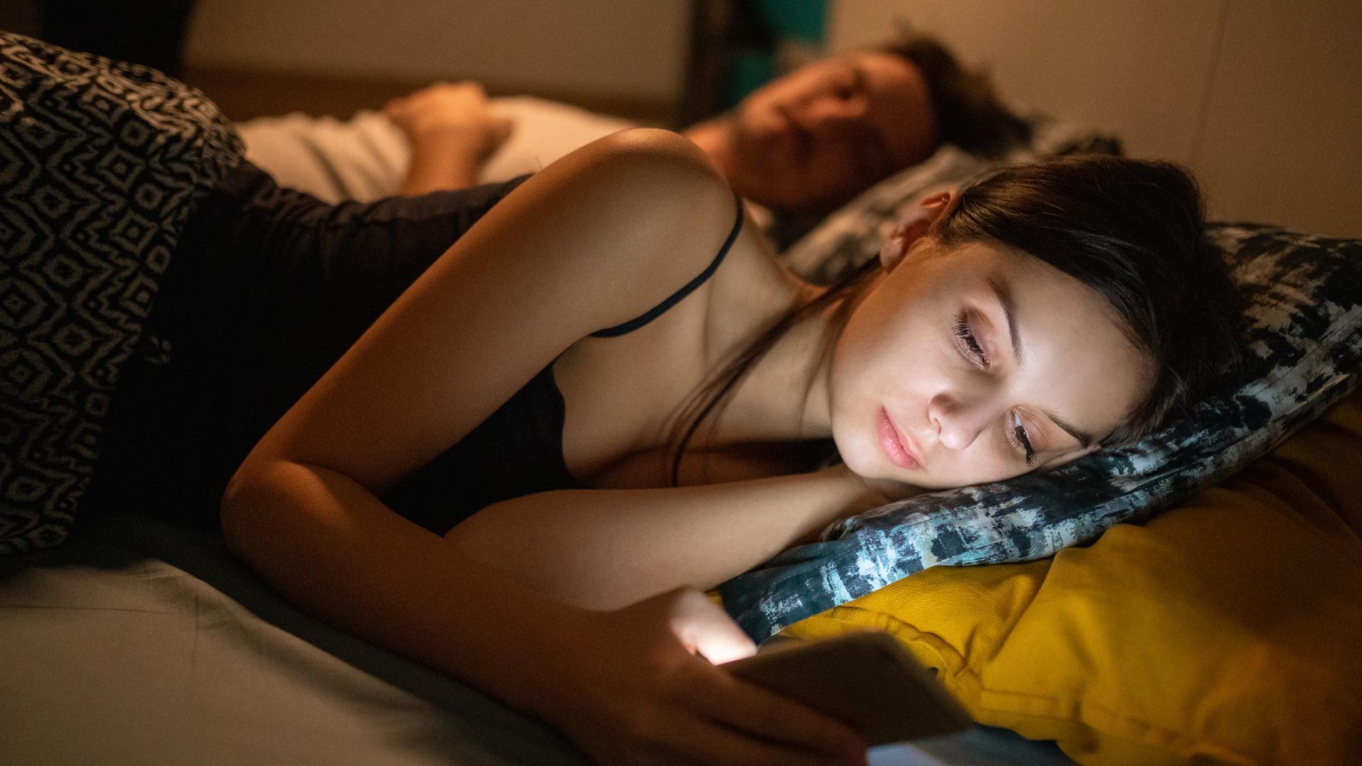 Junge frau am Handy im Bett