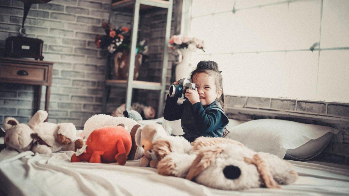 Kind sitzt im Bett mit Kuscheltieren