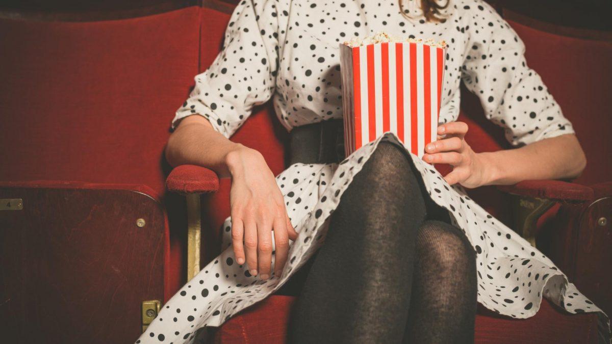 Frau sitzt mit Popcorn in der Hand im Kinosaal