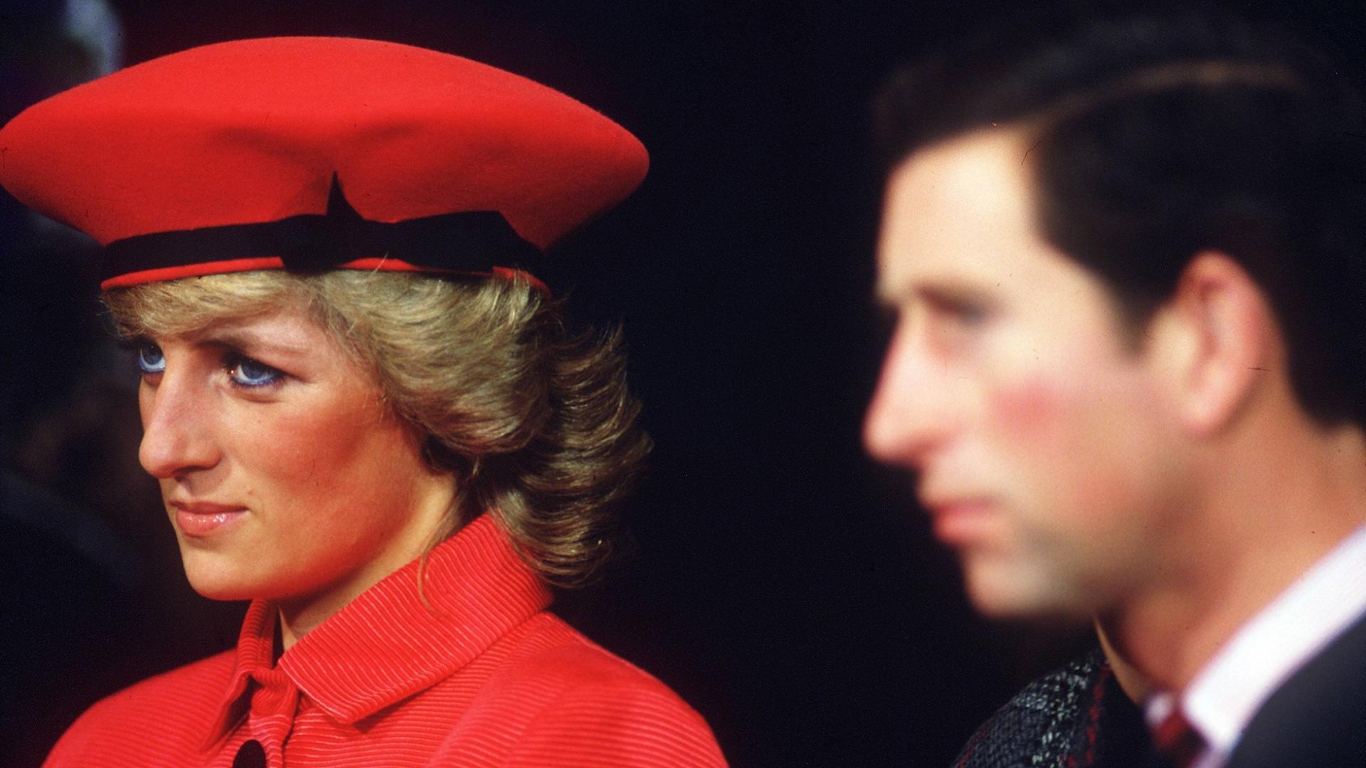 Lady Diana mit roter Mütze und rotem Mantel neben Prinz Charles