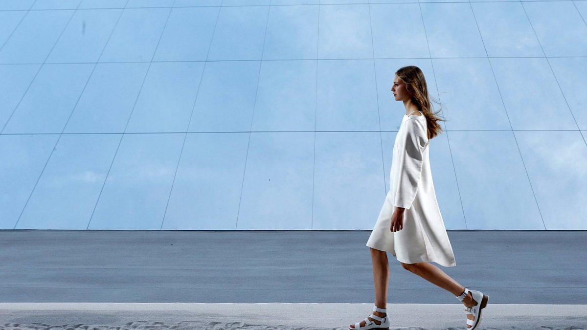 Model in weißen Klamotten vor Fenstern